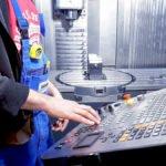 Mitarbeiter bedient eine CNC Fräse
